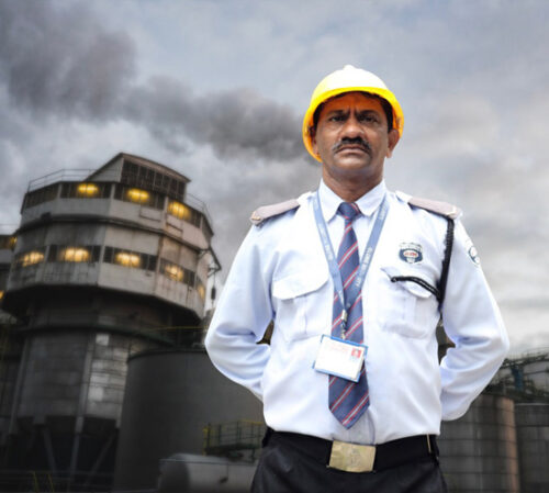 Industrial Security Guard standing with safety helmet outside manufacturing unit